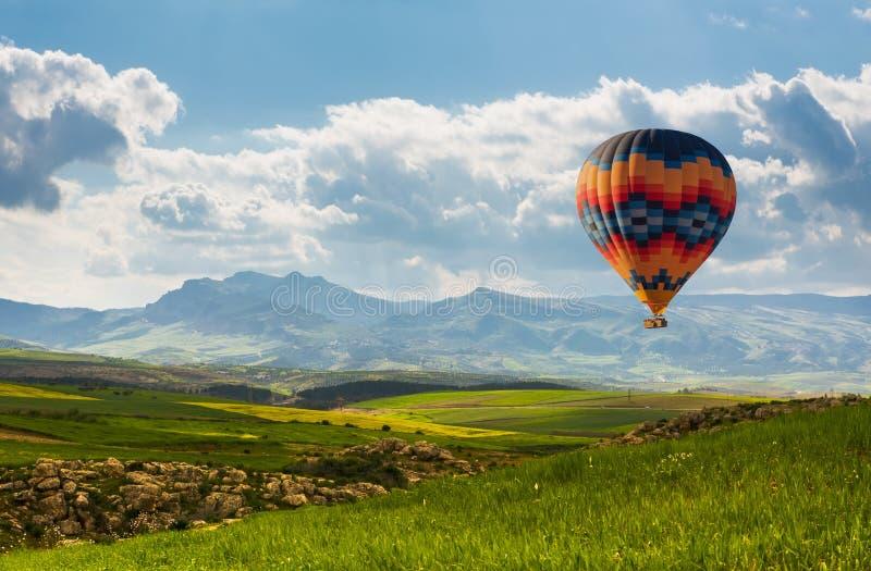 Ζωηρόχρωμο μπαλόνι ζεστού αέρα που πετά πέρα από τον πράσινο τομέα στοκ φωτογραφία