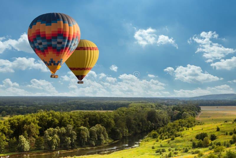 Ζωηρόχρωμο μπαλόνι ζεστού αέρα που πετά πέρα από τον πράσινο τομέα στοκ φωτογραφία με δικαίωμα ελεύθερης χρήσης