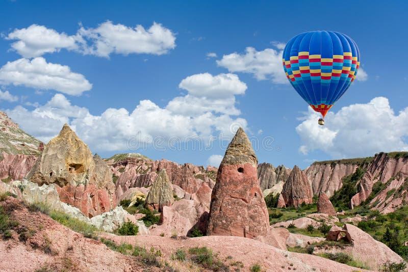 Ζωηρόχρωμο μπαλόνι ζεστού αέρα που πετά πέρα από την κόκκινη κοιλάδα σε Cappadocia, Τουρκία στοκ φωτογραφίες με δικαίωμα ελεύθερης χρήσης