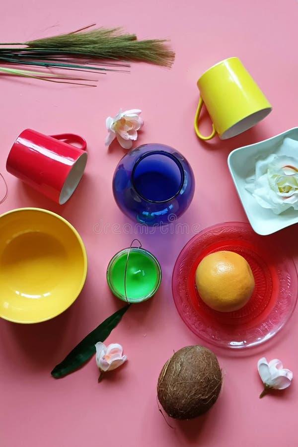 Ζωηρόχρωμο πιάτων κόκκινο φλυτζανιών μπλε κίτρινο φλυτζάνι πιάτων βάζων κίτρινο στο ρόδινο κόκκινο απεικόνισης υποβάθρου εμβλημάτ στοκ φωτογραφίες