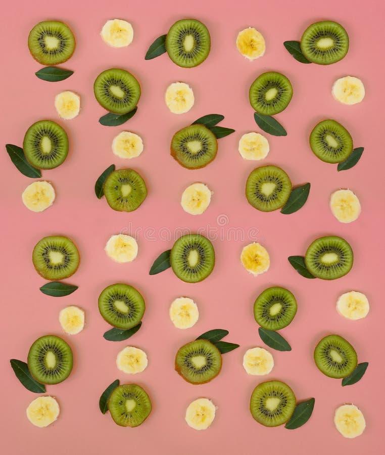 Ζωηρόχρωμο σχέδιο φρούτων των φρέσκων φετών ακτινίδιων και μπανανών στο ρόδινο υπόβαθρο στοκ εικόνες