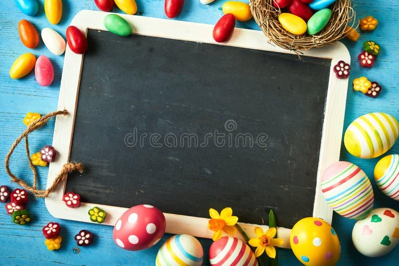 Ζωηρόχρωμο υπόβαθρο αυγών Πάσχας με την κενή πλάκα στοκ φωτογραφία