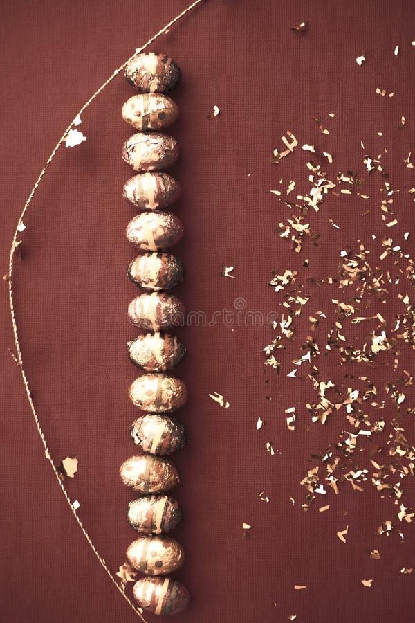 Ζωηρόχρωμο υπόβαθρο Πάσχας Χρυσό κομφετί στα χρωματισμένα φύλλα Χρυσό αυγό Πάσχας στην επιφάνεια Τοπ άποψη των ρυθμίσεων ντεκόρ στοκ εικόνα με δικαίωμα ελεύθερης χρήσης