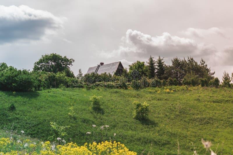Ζωηρόχρωμο φωτεινό ηλιόλουστο τοπίο με το ρωσικό εξοχικό σπίτι στο λόφο σε μια μέση της φωτογραφίας με έναν φωτεινό νεφελώδη ουρα στοκ εικόνα με δικαίωμα ελεύθερης χρήσης