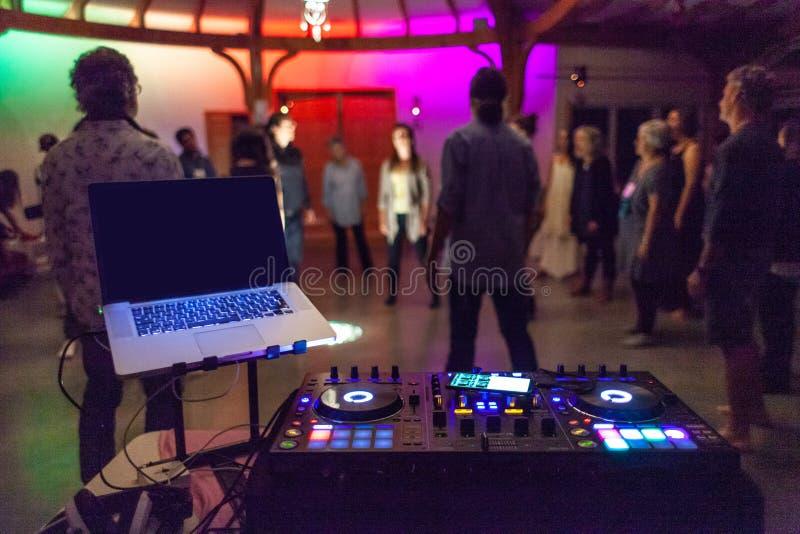 Ζωηρόχρωμο DJ που αναμιγνύει το σταθμό μπροστά από μια μουτζουρωμένη ομάδα ανθρώπων στοκ εικόνα με δικαίωμα ελεύθερης χρήσης
