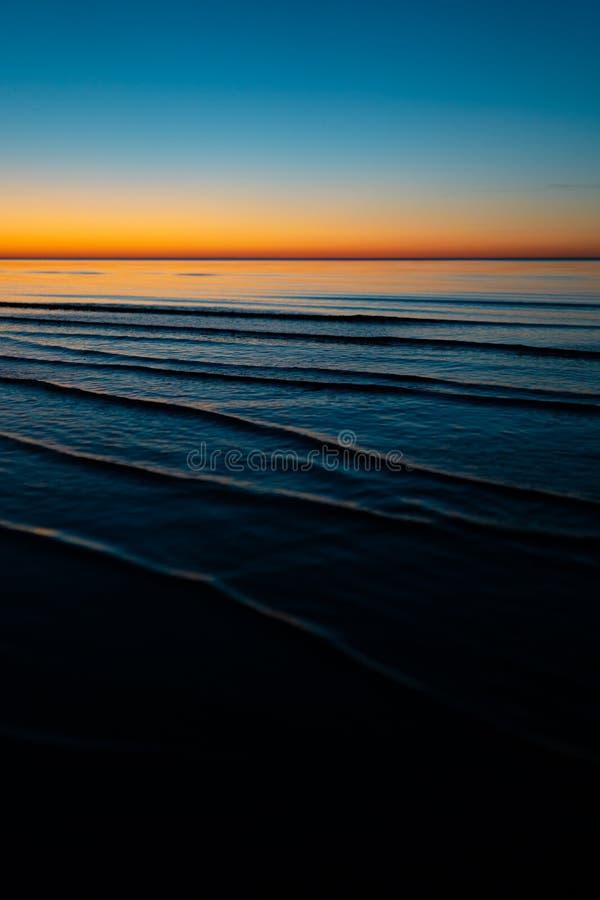 Ζωηρό καταπληκτικό ηλιοβασίλεμα στα κράτη της Βαλτικής - το σούρουπο στη θάλασσα με τον ορίζοντα φωτίζει από τον ήλιο στοκ φωτογραφία