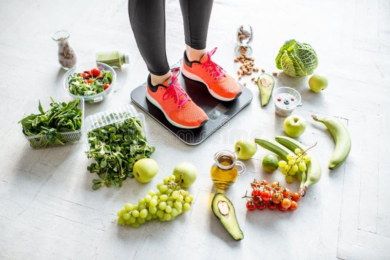 Ζύγισμα αθλητριών με τα υγιή τρόφιμα γύρω στοκ εικόνα με δικαίωμα ελεύθερης χρήσης