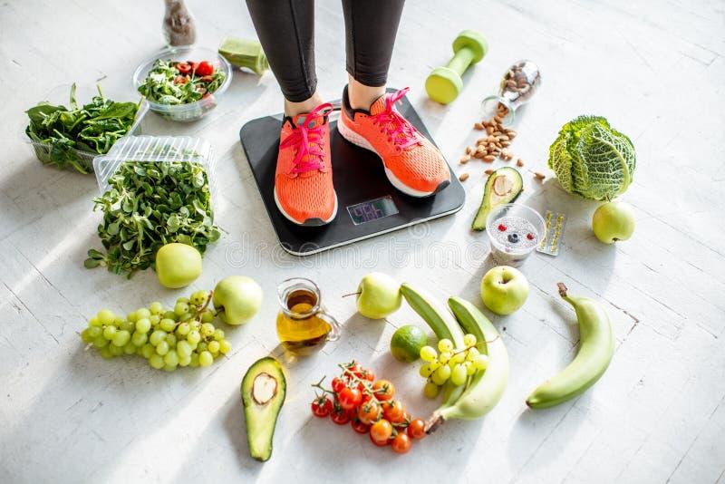 Ζύγισμα αθλητριών με τα υγιή τρόφιμα γύρω στοκ φωτογραφίες