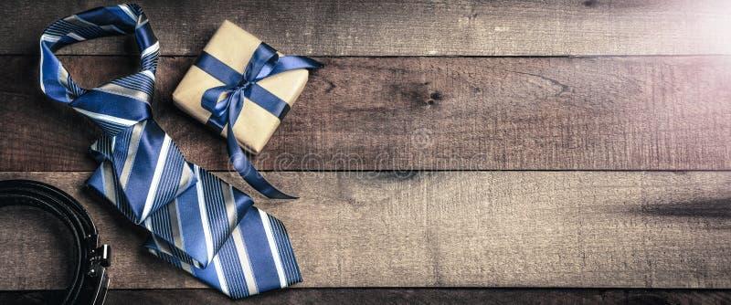 Ζώνη δεσμών και κιβώτιο δώρων στον ξύλινο πίνακα στοκ εικόνες