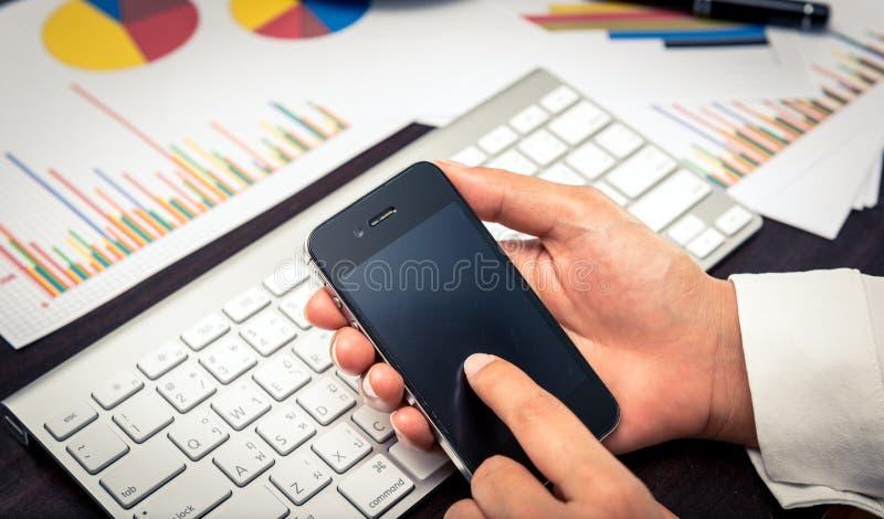 Ηγέτης που έρχεται σε επαφή με την επιχειρησιακή ομάδα του με το smartphone στοκ εικόνα