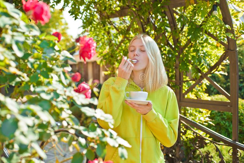 Ηδονισμός και γαστρονομικός Απολαύστε το εύγευστο κρεμώδες cappuccino στον ανθίζοντας κήπο Γαστρονομικό cappuccino ποτών κοριτσιώ στοκ φωτογραφία