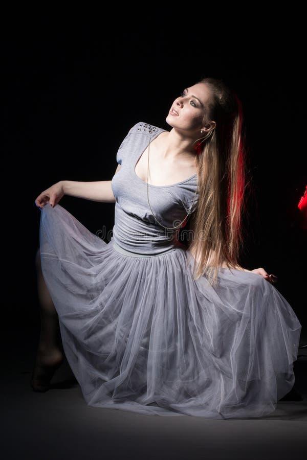 Ηθοποιός σε ένα γκρίζο φόρεμα σε ένα σκοτεινό στάδιο στοκ εικόνες με δικαίωμα ελεύθερης χρήσης