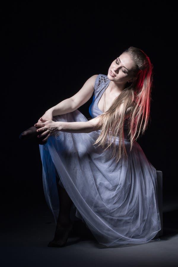 Ηθοποιός σε ένα γκρίζο φόρεμα σε ένα σκοτεινό στάδιο στοκ φωτογραφία με δικαίωμα ελεύθερης χρήσης