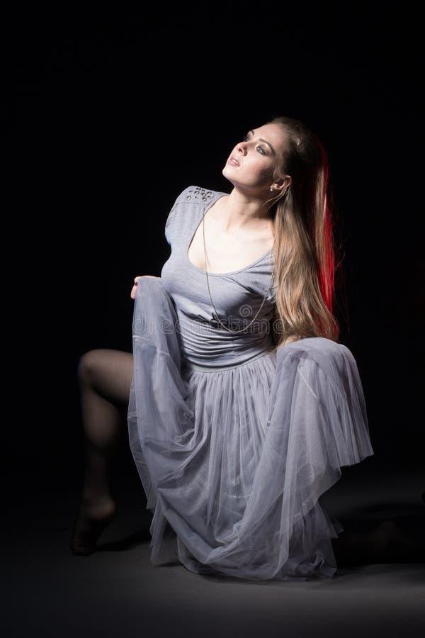 Ηθοποιός σε ένα γκρίζο φόρεμα σε ένα σκοτεινό στάδιο στοκ εικόνα με δικαίωμα ελεύθερης χρήσης