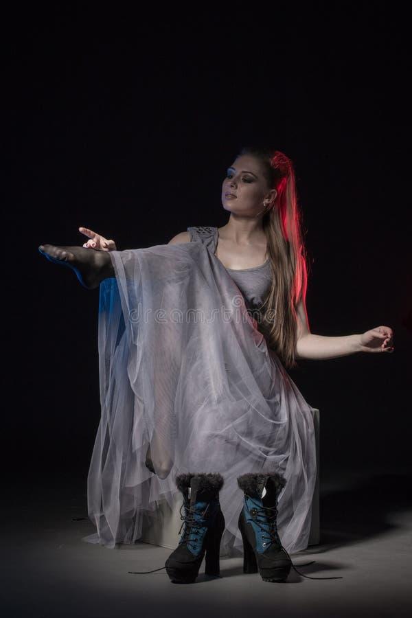 Ηθοποιός σε ένα γκρίζο φόρεμα σε ένα σκοτεινό στάδιο στοκ φωτογραφίες με δικαίωμα ελεύθερης χρήσης