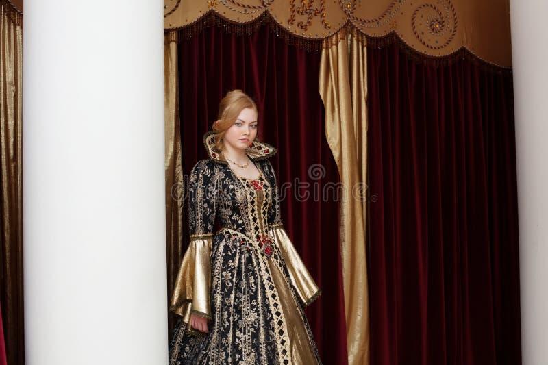Ηθοποιός στη βασιλική τοποθέτηση φορεμάτων στο σκηνικό κουρτινών στοκ φωτογραφία