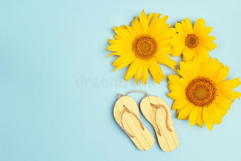 Ηλίανθοι με τα κίτρινα σανδάλια στο μπλε υπόβαθρο με το αντίγραφο spac στοκ φωτογραφία
