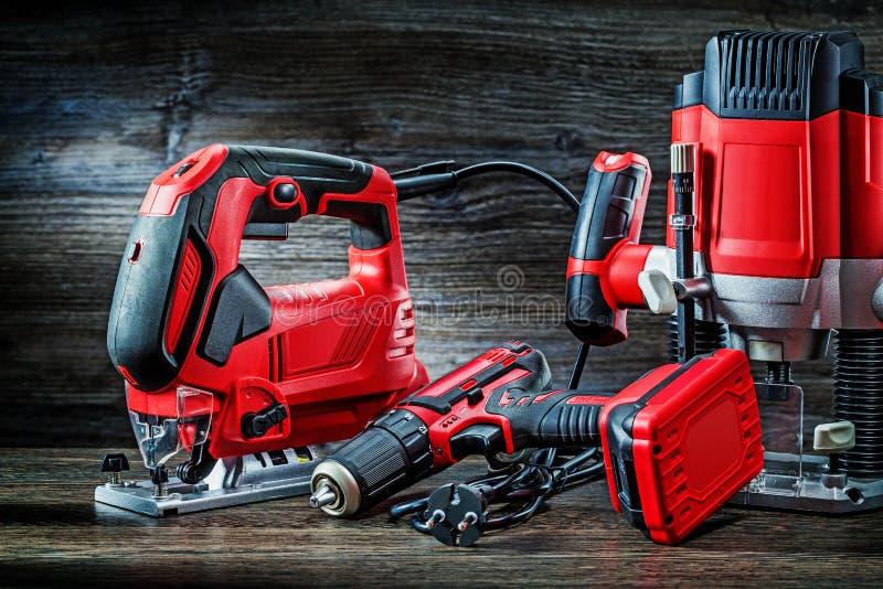 Ηλεκτρικά εργαλεία χεριού με κόκκινα κορδόνια, ασύρματο τρυπάνι με μικρό δρομολογητή εμβόλου και φορητός μίνι δρομολογητής ξύλου  στοκ εικόνα