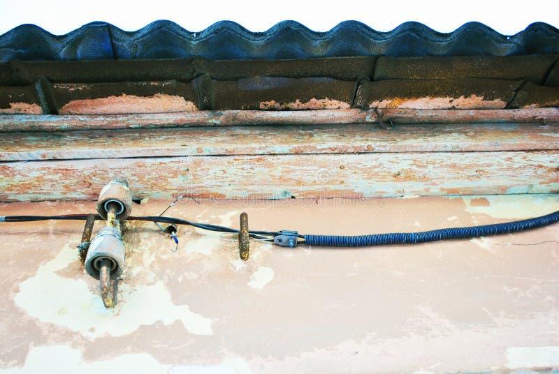 Ηλεκτρικές κεραμικές θρυαλλίδες και μαύρα καλώδια κάτω από τη στέγη πλακών στο ρόδινο shabby χρώμα στοκ φωτογραφία με δικαίωμα ελεύθερης χρήσης