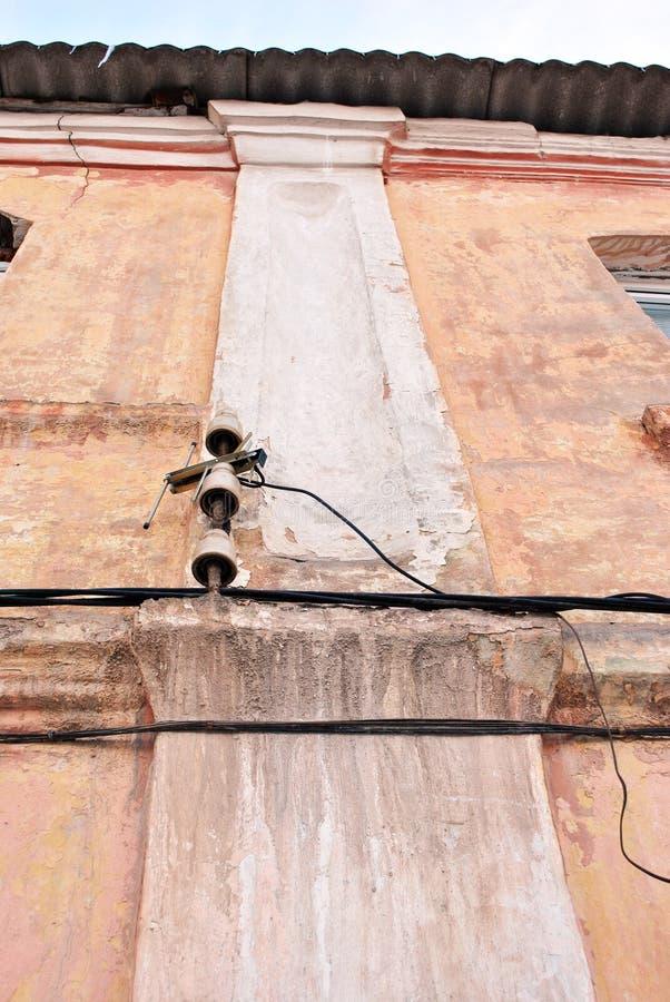 Ηλεκτρικές κεραμικές θρυαλλίδες και μαύρα καλώδια κάτω από τη στέγη πλακών στο ρόδινο shabby οριζόντιο τοίχο χρωμάτων στοκ φωτογραφίες με δικαίωμα ελεύθερης χρήσης