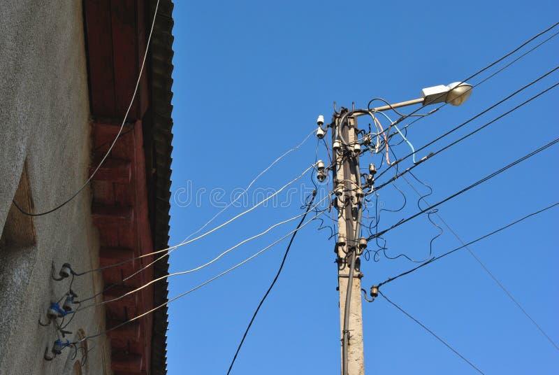 Ηλεκτρικές κεραμικές θρυαλλίδες και μαύρα καλώδια κάτω από τη στέγη πλακών στον τοίχο και το παλαιό φανάρι, άποψη από το έδαφος π στοκ φωτογραφία