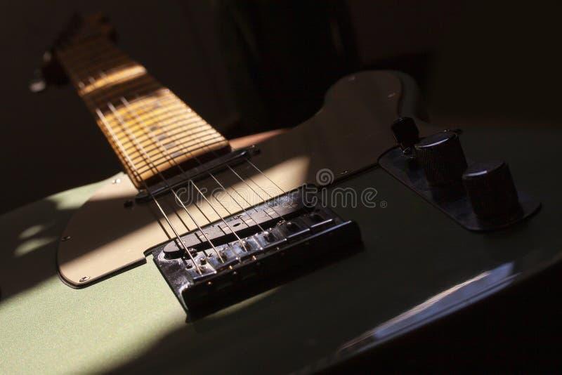 Ηλεκτρική κιθάρα στο δημιουργικό φωτισμό με τις σκιές, εικόνα κινηματογραφήσεων σε πρώτο πλάνο στοκ εικόνα με δικαίωμα ελεύθερης χρήσης