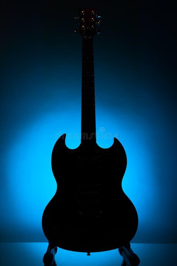 Ηλεκτρική σκιαγραφία κιθάρων στο μπλε κλίμα στοκ φωτογραφία