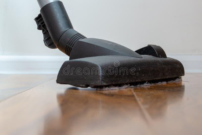 Ηλεκτρική σκούπα στο πάτωμα που παρουσιάζει καθαρισμό σπιτιών στοκ φωτογραφίες
