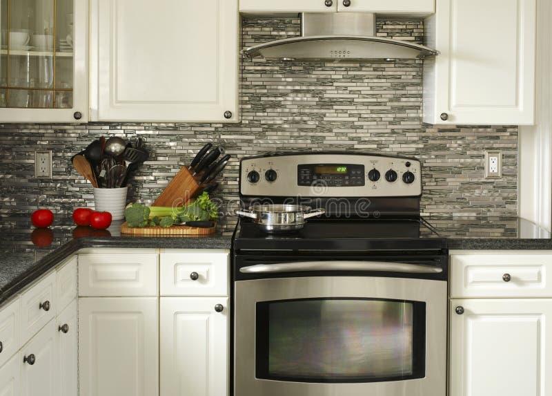 Ηλεκτρική σόμπα ανοξείδωτου, εργαλεία κουζινών και λαχανικά στοκ φωτογραφίες