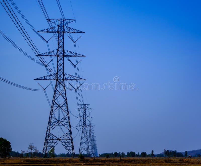 Ηλεκτρικοί πόλοι τάσης και ηλεκτρικά καλώδια, ζώνη κινδύνου πέρα από τους ξηρούς τομείς στο τοπίο επαρχίας της Ταϊλάνδης στοκ φωτογραφία