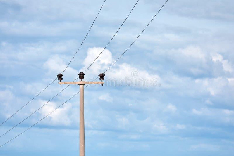 Ηλεκτρικοί πόλος δύναμης υψηλής τάσης, ηλεκτροφόρα καλώδια και θρυαλλίδες σε ένα νεφελώδες κλίμα μπλε ουρανού στοκ εικόνες με δικαίωμα ελεύθερης χρήσης