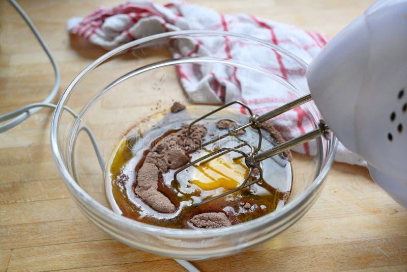 Ηλεκτρικός αναμίκτης σε ένα κύπελλο γυαλιού με τη ζύμη κέικ του αυγού, του κακάου και του αλευριού σε έναν ξύλινο πίνακα με μια π στοκ φωτογραφία με δικαίωμα ελεύθερης χρήσης