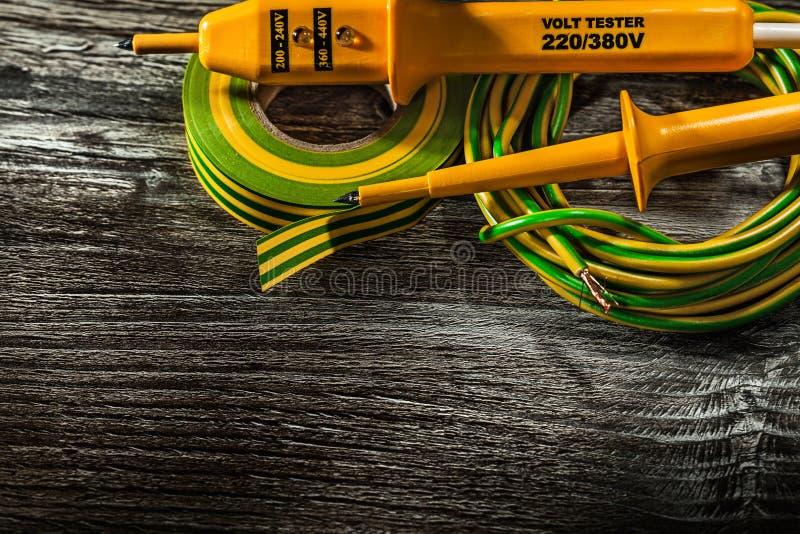 Ηλεκτρικός ελεγκτής hunk της κυλημένης ταινίας μόνωσης καλωδίων στο ξύλινο β στοκ φωτογραφία