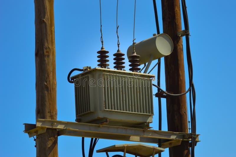 Ηλεκτρικός μετασχηματιστής στους ξύλινους πυλώνες στοκ εικόνα με δικαίωμα ελεύθερης χρήσης