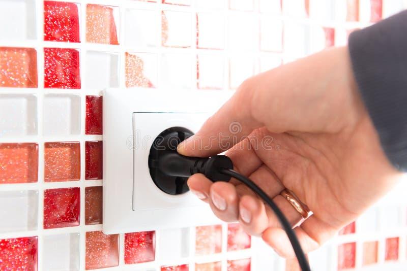 Ηλεκτρικό βύσμα σε ένα χέρι γυναικών στοκ εικόνα με δικαίωμα ελεύθερης χρήσης