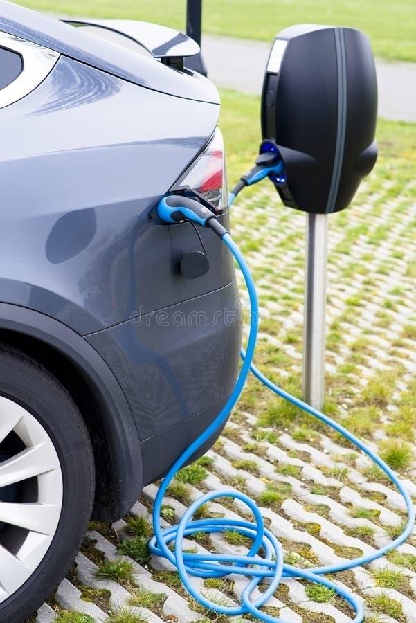 Ηλεκτρικό νέο αυτοκίνητο που συνδέεται για τη χρέωση στον υπαίθριο σταθμό στοκ φωτογραφία με δικαίωμα ελεύθερης χρήσης