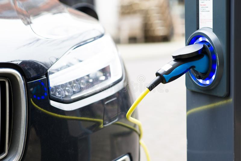 Ηλεκτρικό νέο αυτοκίνητο που συνδέεται για τη χρέωση στον υπαίθριο σταθμό στοκ φωτογραφίες με δικαίωμα ελεύθερης χρήσης