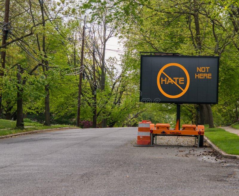 Ηλεκτρικό σημάδι οδών κυκλοφορίας στην ήρεμη οδό γειτονιάς που δεν λέει κανένα μίσος, όχι εδώ στοκ εικόνες