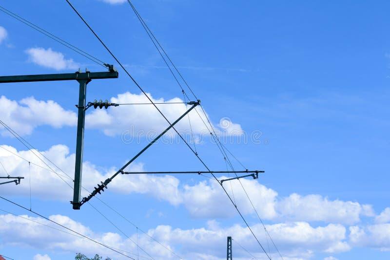 Ηλεκτρικό υπερυψωμένο σύστημα ηλέκτρισης σιδηροδρόμων γραμμών τραίνων με τα καλώδια και το μπλε ουρανό ανωτέρω στοκ φωτογραφία