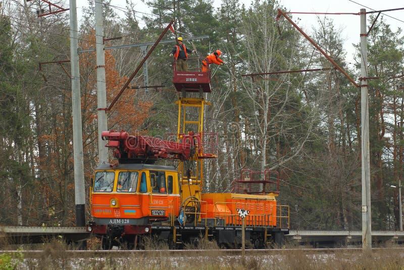 Ηλεκτρολόγοι που καθορίζουν τα ηλεκτροφόρα καλώδια και που εργάζονται στο ύψος στο τραίνο υπηρεσιών σιδηροδρόμου επικίνδυνη εργασ στοκ φωτογραφία με δικαίωμα ελεύθερης χρήσης