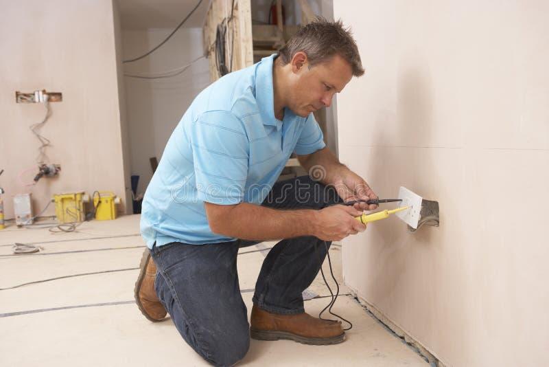 Ηλεκτρολόγος που εγκαθιστά την υποδοχή τοίχων στοκ φωτογραφία