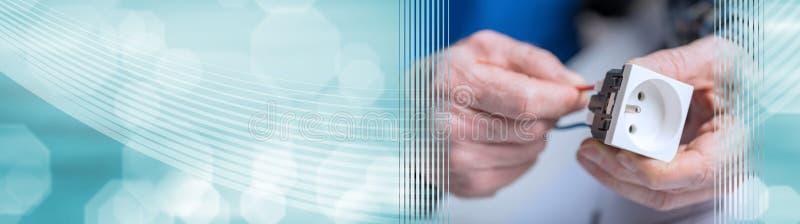 Ηλεκτρολόγος που συνδέει ένα καλώδιο με μια υποδοχή δύναμης έμβλημα πανοραμικό στοκ εικόνες
