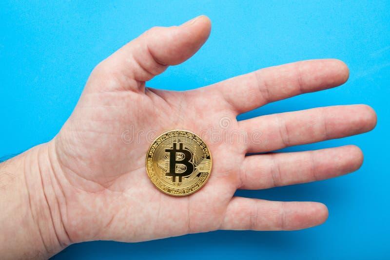 Ηλεκτρονικό crypto νόμισμα bitcoin υπό εξέταση σε ένα μπλε υπόβαθρο στοκ εικόνες με δικαίωμα ελεύθερης χρήσης