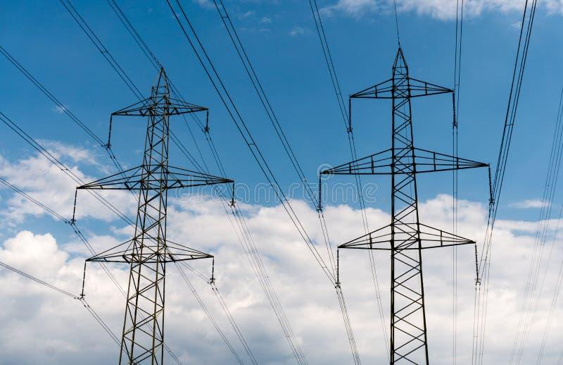 Ηλεκτροφόρα καλώδια και πυλώνες στη σκιαγραφία ενάντια σε έναν μπλε ουρανό με τα άσπρα σύννεφα στοκ εικόνα