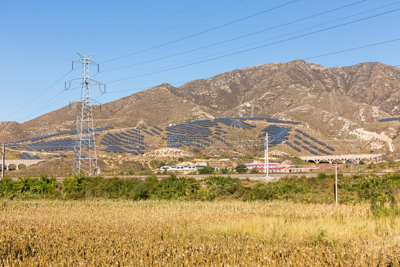 Ηλεκτροφόρο καλώδιο υψηλής τάσης και ηλιακά πλαίσια στο βουνό, Κίνα στοκ εικόνες