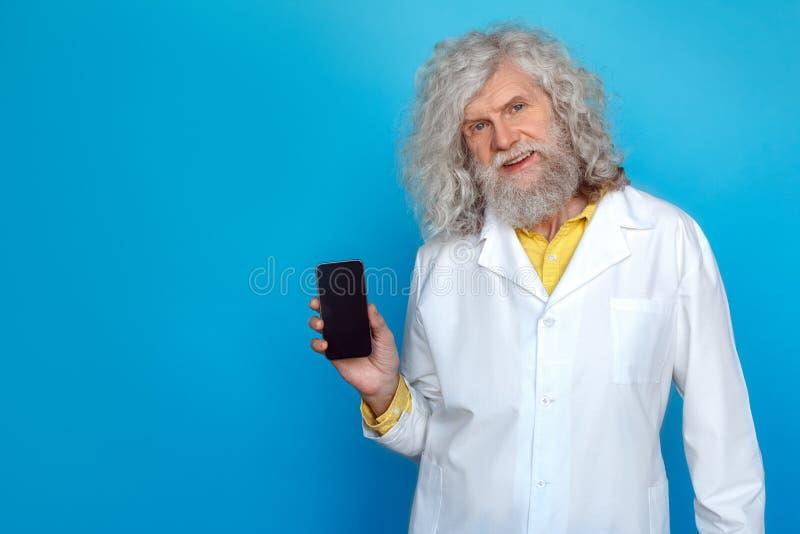 Ηληκιωμένος που φορά το στούντιο εσθήτων του γιατρού που απομονώνεται στο μπλε που παρουσιάζει smartphone στο χαμόγελο καμερών φι στοκ εικόνες με δικαίωμα ελεύθερης χρήσης