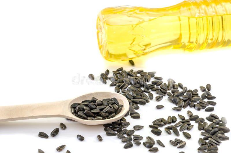 Ηλιέλαιο σε ένα μπουκάλι και τους σπόρους σε ένα ξύλινο κουτάλι στοκ φωτογραφία