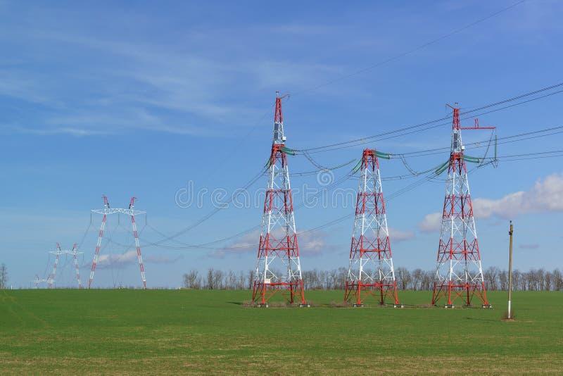 Τα ηλεκτροφόρα καλώδια υποστηρίξεων είναι στον τομέα Κόκκινος και άσπρος ενάντια σε έναν φωτεινό μπλε ουρανό Ηλιακά πλαίσια για τ στοκ εικόνα