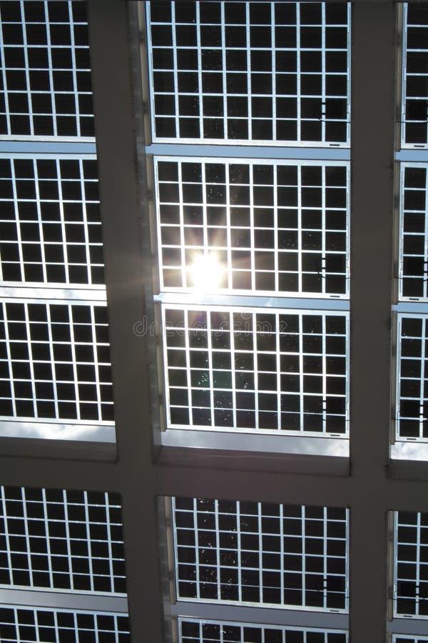 Ηλιακή ισχύς - επιτροπές ενάντια στο μπλε ουρανό και τον ήλιο στοκ φωτογραφία