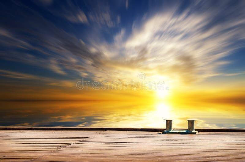 Ηλιακή πτώση στη θάλασσα, ένα είδος από μια ξύλινη πρόσδεση στοκ φωτογραφία